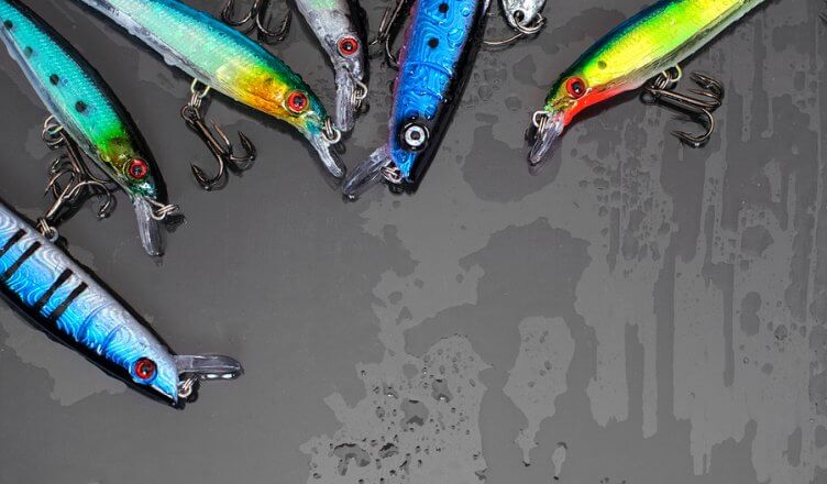 Colorful Fishing Lures on black glass background